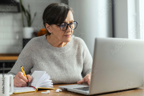 Concentrated retirement woman using a laptop sitting at the desk in the kitchen for remote work, studying online, watching a webinar and takes a notes Fototapet