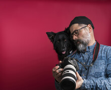 Man Watching Camera Photos With His Dog In A Studio On A Red Background