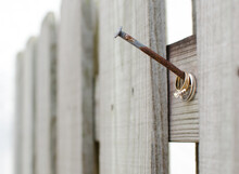 A Set Of Wedding Rings Hanging From An Old Fence On A Rusty Nail