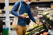 Midsection Of Man Wearing Face Mask Buying Granny Smith Apples In Supermarket