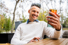 Smiling Man Taking Selfie On Smart Phone While Sitting In Outdoor Cafe