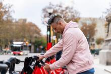 Stylish Man Renting Bicycle Through Smart Phone At Parking Station