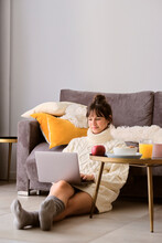 Woman In Sweater Using Laptop While Sitting On Floor In Living Room At Home