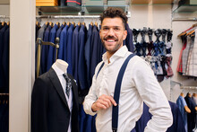 Portrait Of Smiling Man In White Shirt And Blue Suspendersin Tailors Boutique