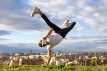 Flexible Young Man Wearing Virtual Reality Headset While Doing Handstand On Hill In City Against Sky