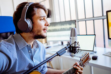 Male Singer With Headphones And Microphone Singing While Playing Guitar At Recording Studio