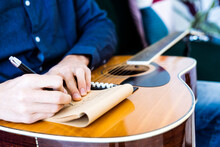 Song Writer Writing Music On Note Pad While Sitting With Guitar At Studio