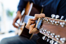 Musician Playing Acoustic Guitar While Sitting At Studio