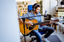 Guitarist Playing Guitar While Sitting By Microphone Stand At Recording Studio