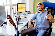 Happy Musician With Laptop Holding Camera While Sitting At Recording Studio