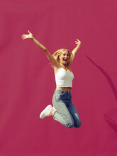 Carefree Woman With Hand Raised Jumping Against Wall On Sunny Day