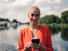 Confident Businesswoman With Smart Phone Against Lake On Sunny Day