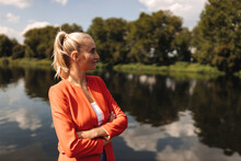Female Entrepreneur With Arms Crossed Looking Away While Standing By Lake