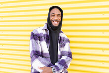 Smiling Male Rapper Standing Against Yellow Corrugated Wall
