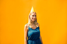 Attractive Woman Wearing Party Hat Against Wall On Sunny Day