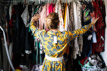 Fashionable Blond Woman In New Yellow Dress Choosing From Clothes Rack At Apartment