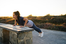 Young Woman Practicing Push-ups On Bench Against Clear Sky At Sunset
