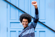 Cheerful Young Man With Arm Raised Screaming While Standing Against Blue Wall