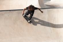 Curly Hair Sportsman Practicing Skateboarding On Sports Ramp At Skateboard Park