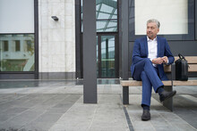 Senior Businessman Waiting While Sitting With Legs Crossed At Bus Stop In City