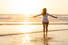 Carefree Woman With Arms Outstretched Running Toward Sea During Sunset