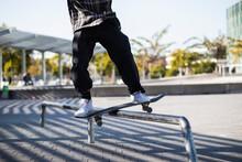 Man Balancing While Standing With Skateboard Over Hurdle At Skateboard Park
