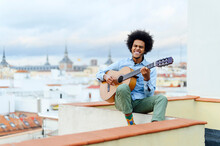 Young Man With Eyes Closed Playing Acoustic Guitar While Sitting On Terrace