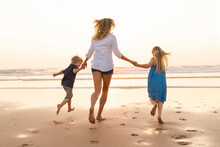 Children Holding Hands Of Mother While Running At Beach During Sunset