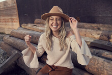 Excited Beautiful Woman With Eyes Closed Gesturing While Sitting On Woodpile