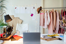 Laptop On Desk By Clothes Rack At Atelier