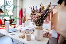 Flower In Vase By Candle On Desk At Design Studio