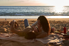 Smiling Couple Talking While Resting On Beach