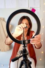Female Fashion Designer Adjusting Circle Light For Vlogging At Atelier