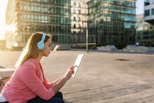 Spain, Barcelona, Young Woman With Headphones Using Digital Tablet In City