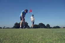 Friends Playing Golf Against Clear Blue Sky On Course