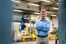 Confident Manager With Arms Crossed Standing In Industry