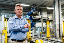 Mature Male Professional With Arms Crossed Standing In Industry
