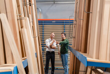 Two Carpenters Talking In Production Hall With Wooden Planks In Foreground