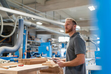 Portrait Of Carpenter Standing In Production Hall With Clipboard In Hands