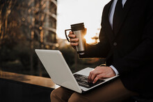 Businessman With Thermos Using Laptop While Sitting On Retaining Wall During Sunset