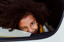 Close-up Portrait Of Girl Winking Eye In Car