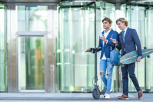 Male Colleagues Holding Mobile Phone While Walking With Skateboard And Push Scooter On Sidewalk