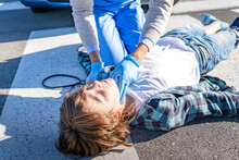 Doctor Checking Unconscious Boy Lying On Road After Car Accident