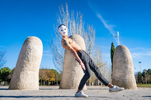 Shirtless Man Wearing White Mask Dancing While Standing On Footpath