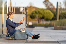 Cheerful Businessman With Laptop On Video Call While Sitting On Skateboard During Sunny Day