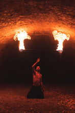 Young Man Performing With Fire Staff In Tunnel