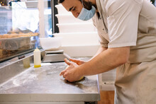 Mid Adult Male Chef Kneading Bread Dough On Counter In Commercial Kitchen