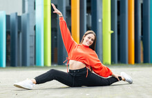 Portrait Of Beautiful Brunette Doing Splits In Front Of Colorful Building