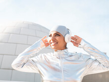 Smiling Woman Wearing Protective Suit Listening Music While Standing Against Igloo
