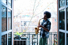Afro Male Musician Practicing Saxophone In Balcony At Home